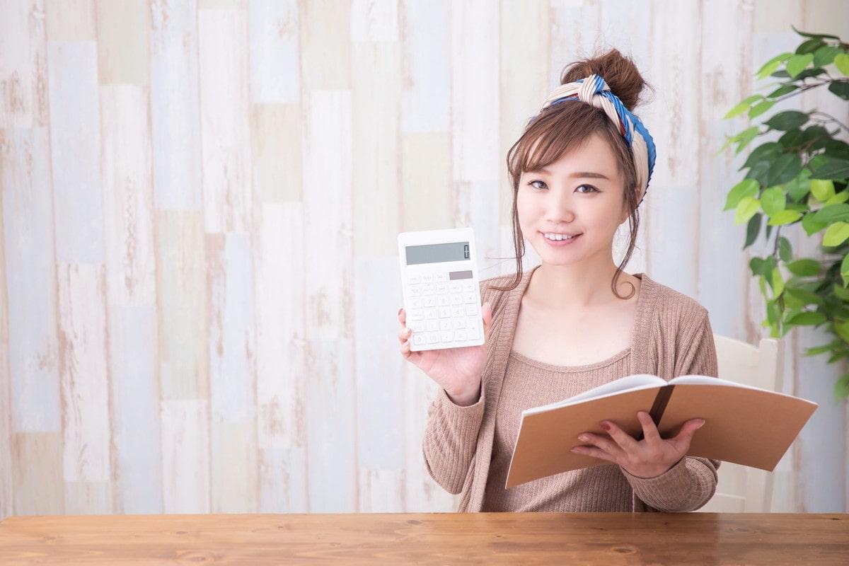 電卓で計算をする若い女性