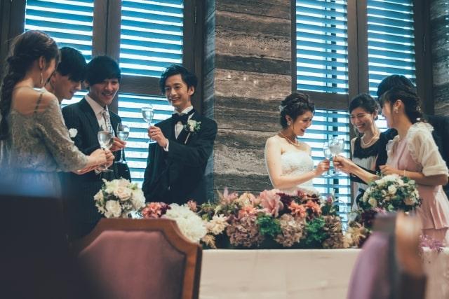 披露宴で談笑する笑顔のゲストと新郎新婦さま