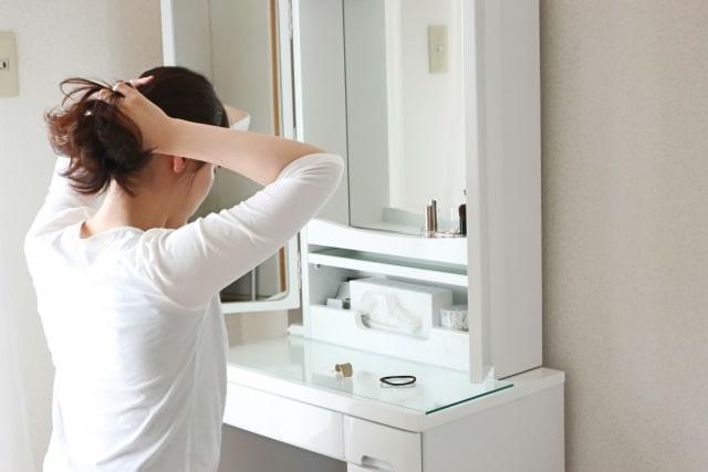 化粧台の前で身支度をする女性