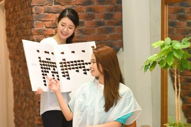 美容室でカラーレベルを選ぶ女性