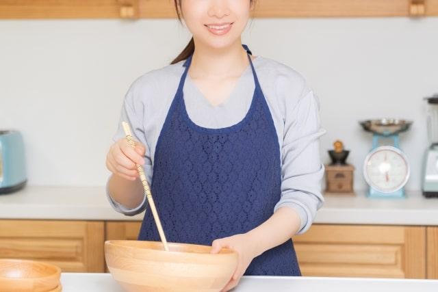 エプロンをつけて料理をする女性