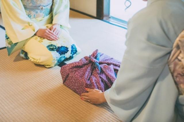 着物で手土産を渡す女性
