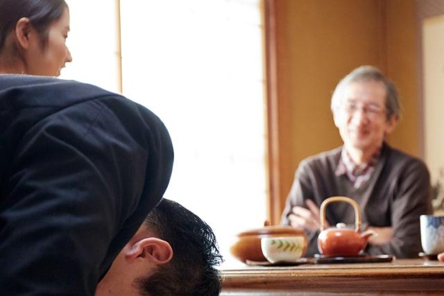 結婚挨拶で頭を下げる男性に笑顔をむける父親