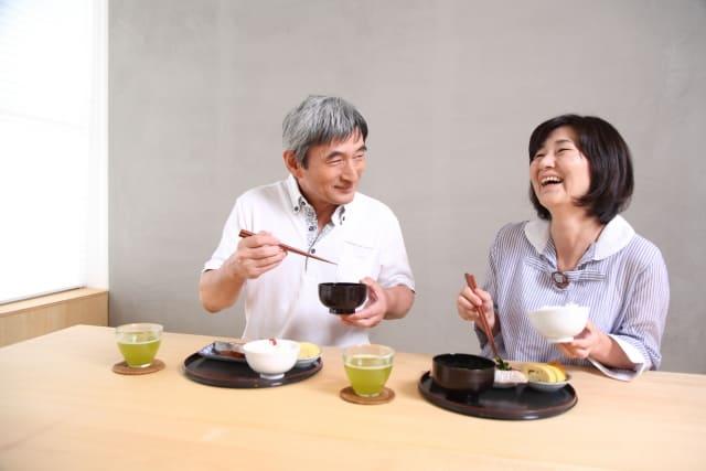 笑顔で食事をするご年配の夫婦