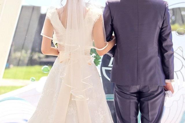 挙式で腕を組む新郎新婦様