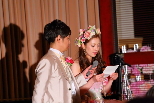 花嫁の手紙でマイクを持つ新郎と手紙を読む新婦