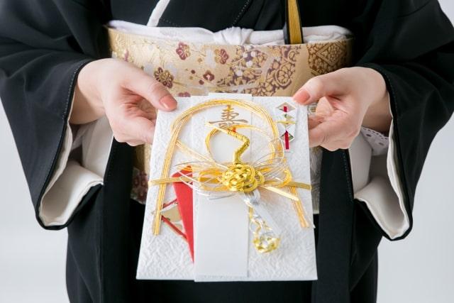 結婚式のご祝儀を差し出す人