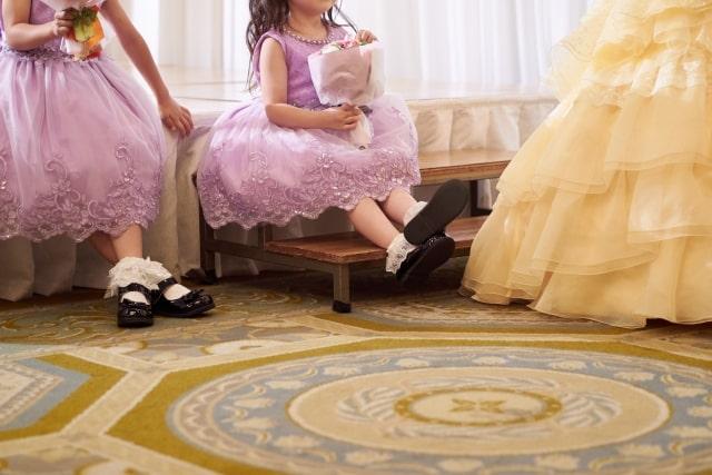結婚式場の控室でゆっくりするドレスアップした子ども