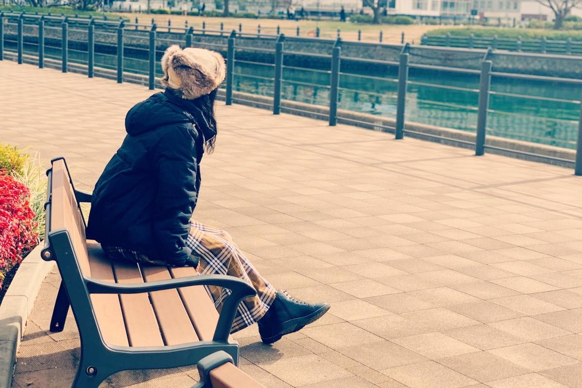 ひとりでベンチに座る女性