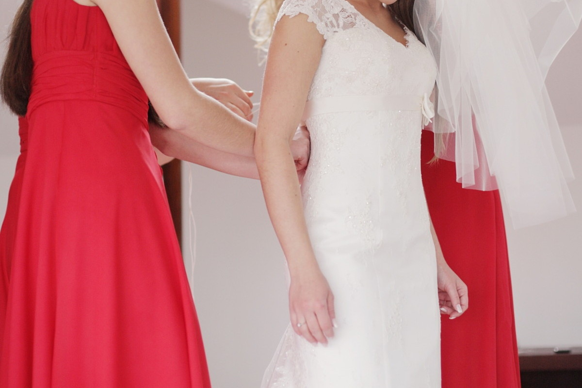 花嫁さまのサポートをする赤いドレスのブライズメイド