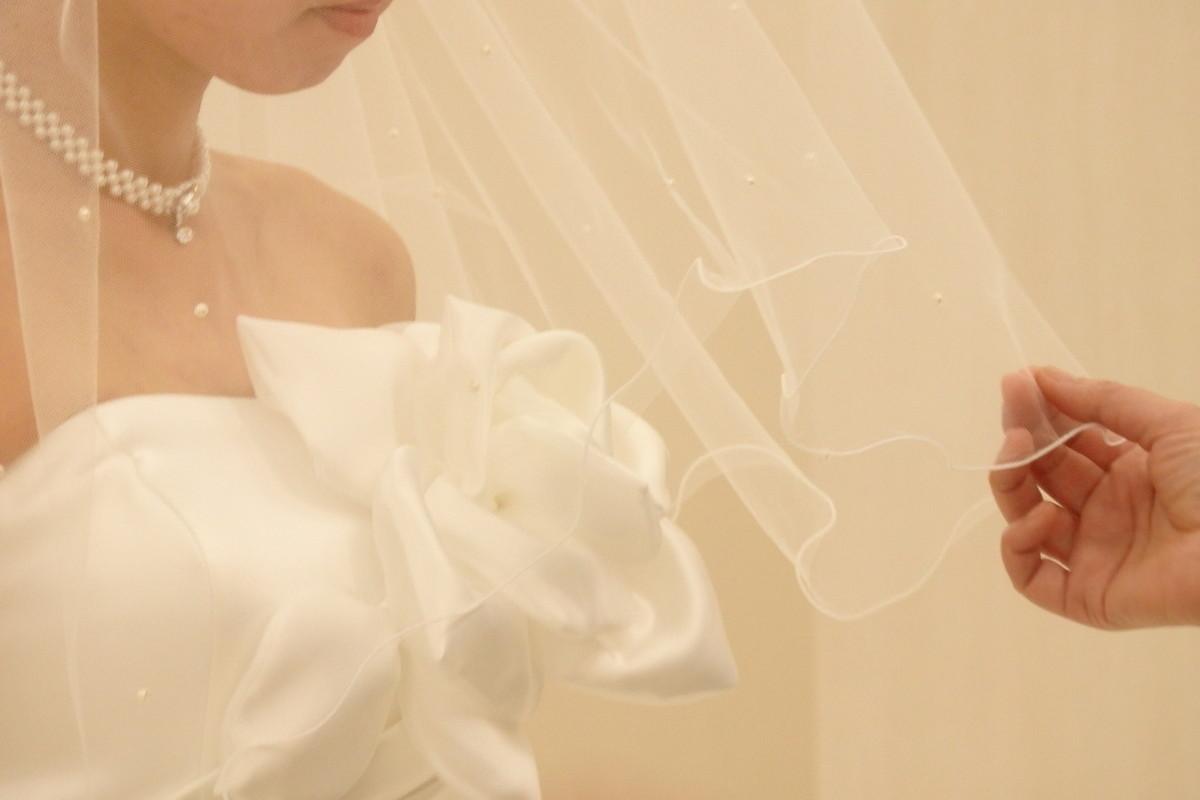 花嫁さまのベールに手をかける母親の手