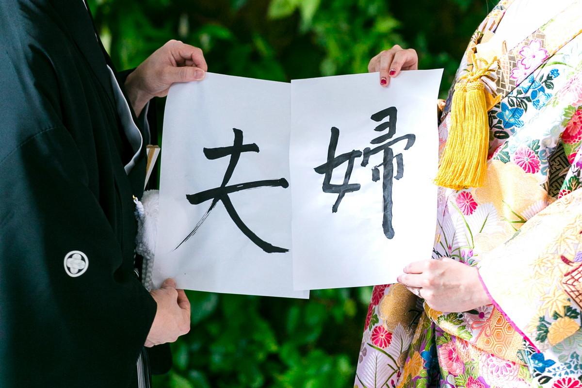 夫婦と書いた紙を持つ新婚カップル