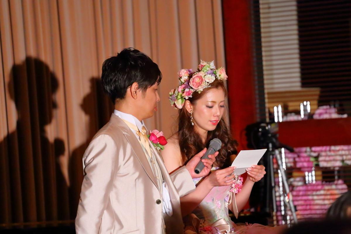 花嫁の手紙でマイクを持つ新郎さまと手紙を読む花嫁さま